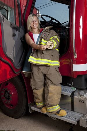 A female firefighter standing in the door of a fire truck. Фото со стока