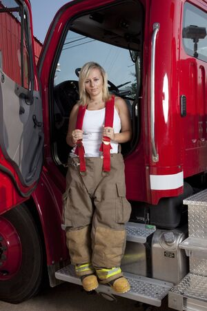 A female firefighter standing in the door of a fire truck. Stok Fotoğraf