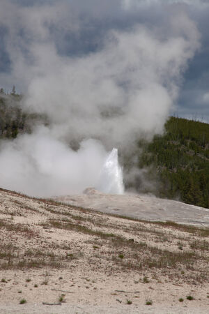 spew: Old Faithful beginning to spew at Yellowstone National Park.