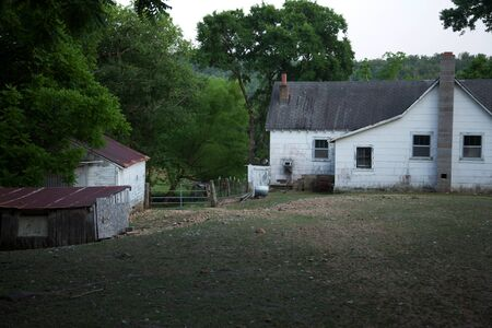 A side view of an old white farm house.