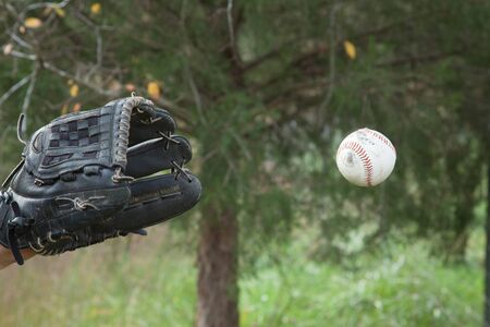 A baseball flying towards a baseball glove.