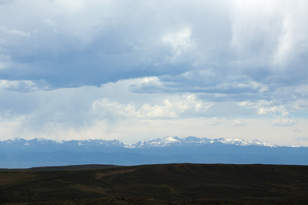Distant snow covered mountains under a cloudy sky.