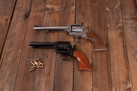 Two revolvers with bullets on a wooden background.