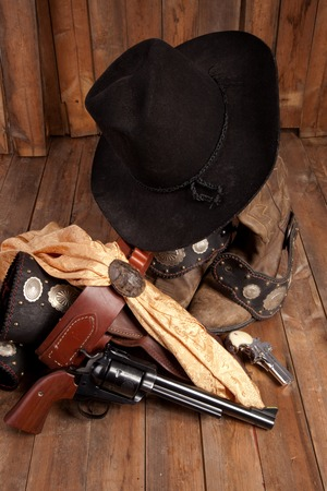 A bunch of cowboy equipment on a wooden background.