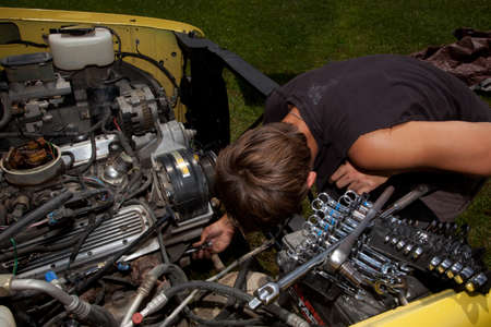 A teenager working on a truck engine. Editorial