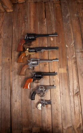 A group of pistols on a wooden background. Reklamní fotografie