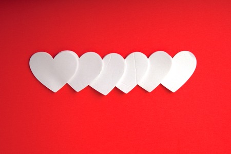 White foam hearts on a red background. Banque d'images