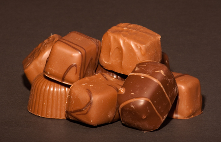 A group of chocolates on a black background. Stock Photo