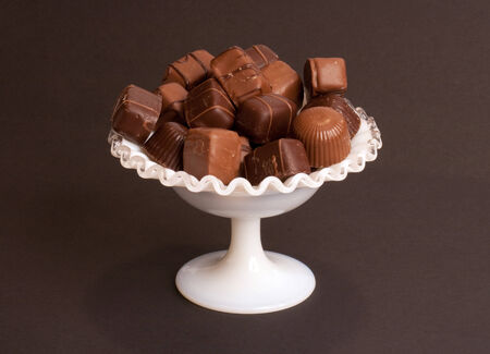 A pile of chocolates in a white dish. Stock Photo