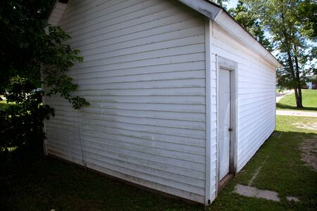A side view of a small white building.