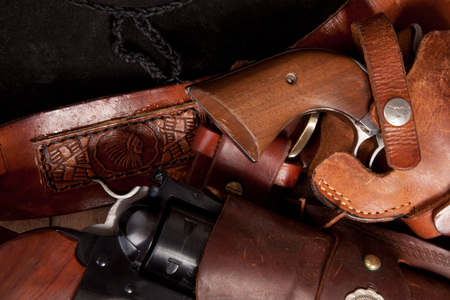 A close up of two revolvers in holsters.