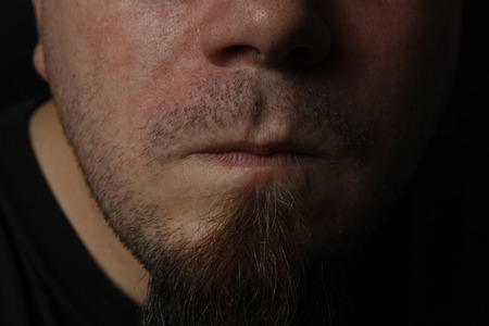 A close up of a mans mouth and chin.