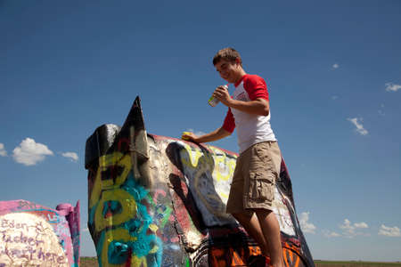 A teenage boy spray painting cars at Cadillac Ranch. Stock Photo