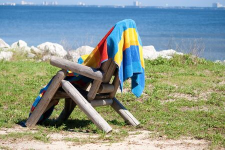 A beach towel drying on the back of a chair.