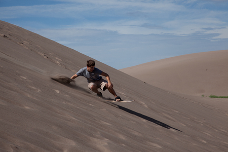 A teenage boy sandboarding at the Great Sand Dunes National Park. Reklamní fotografie - 57872694