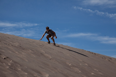 A teenage boy sandboarding at the Great Sand Dunes National Park.