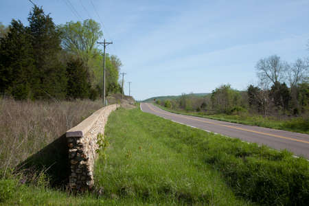 A stone fence along a rural road.