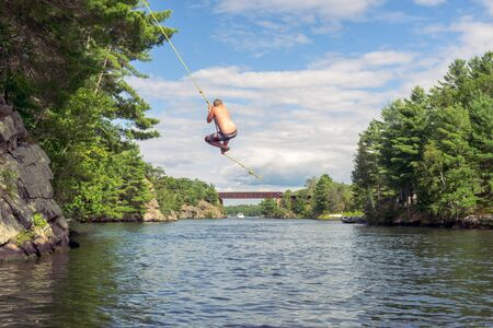 Swinging out over water on a rope