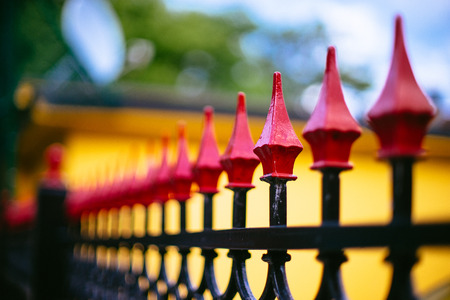 Red topped wrought iron fence 版權商用圖片