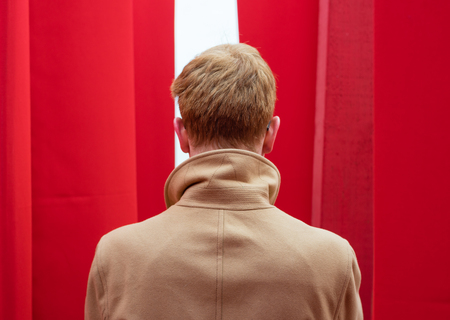Man in a coat peers out from behind red curtains Imagens