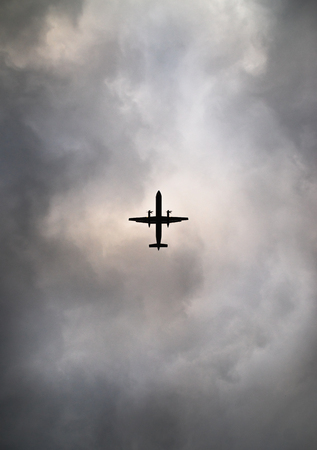 Commuter airplane silhouetted against cloudy sky Stock Photo