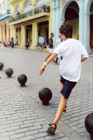 Young boy runs along cobblestone street Imagens