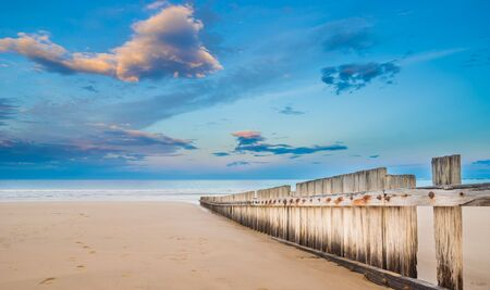 A wooden fence on an empty beach at sunset