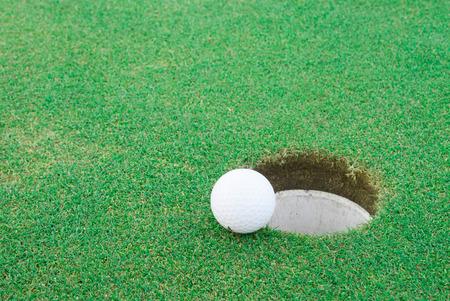 A golf ball very close to a hole