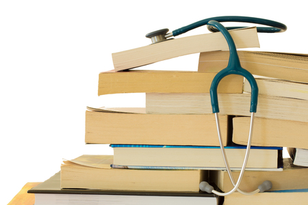 A stethoscope resting on a stack of text books
