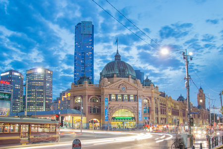 busy street: MELBOURNE, AUSTRALIA - MARCH 14 2014: Flinders Street Station in Melbourne at night with a Melbourne tram in the foreground. Editorial