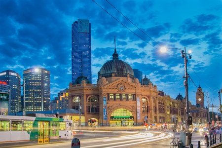 flinders: MELBOURNE, AUSTRALIA - MARCH 14 2014: Flinders Street Station in Melbourne at night with a Melbourne tram in the foreground. Editorial
