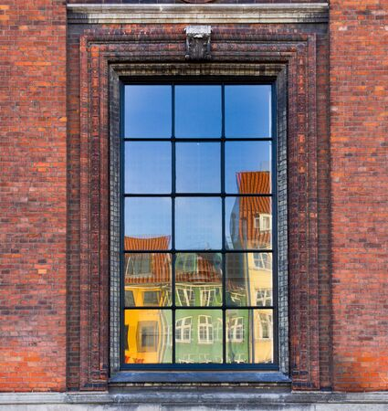 The colorful buildings of Nyhavn, Copenhagen reflected in a window