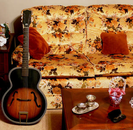 davenport: Parlor furniture scene with acoustic guitar leaning against arm of couch.