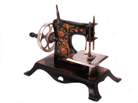 Highly decorated black all steel antique child's crank toy sewing machine Stockfoto