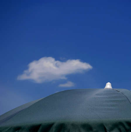 Close up of green beach umbrella with blue sky and one cloud background 版權商用圖片