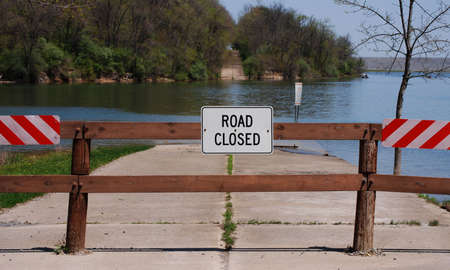disappears: Warning sign and barrier where old highway disappears into a lake and reappears from the water in the background.