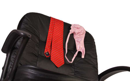 red bra: Red mens necktie and ladys bra draped over the back of a black office desk chair. Stock Photo