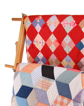 Detail view of two multicolor quilts hanging on a wooden display rack. Reklamní fotografie - 1518066