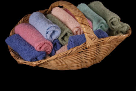 A selection of pastel colored terrycloth wash cloths rolled and stacked in a wicker basket, black iso.