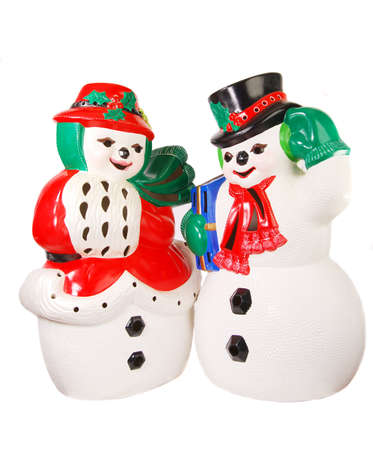 mr: Handpainted ceramic figures of Mr. and Mrs. Snowman bundled up against the cold; Mr. carries a wrapped gift. Stock Photo