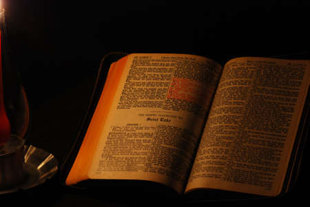 Holy Bible opened to Gospel of St. Luke, illuminated with a single red candle. photo