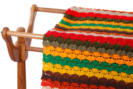 Crocheted afghan hanging on a wooden display rack.