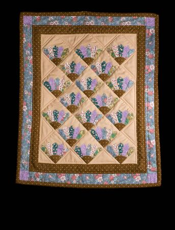Tan and blue fan pattern quilt on a black isolation.