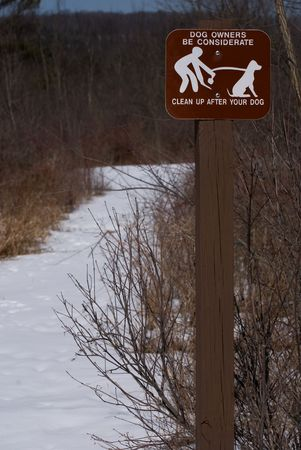 Dog cleanup sign on walking trail in winter.
