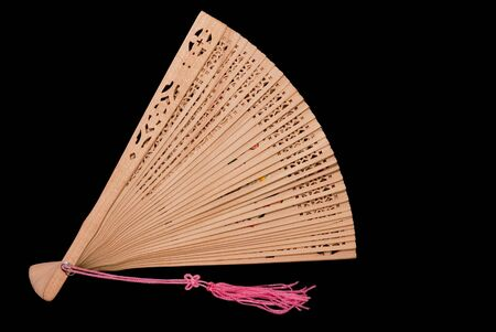 Partially opened bamboo fan with pink tassel, black iso.