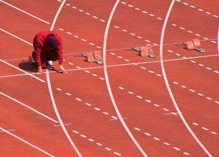 Runner preparing at the start line of track meet Stock Photo
