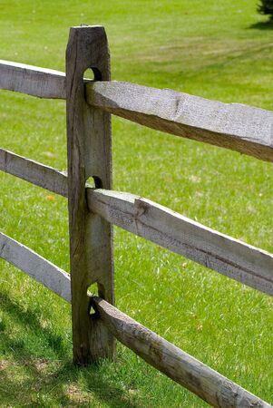 Detail view of wooden split rail fence, lawn background. Reklamní fotografie - 2927485