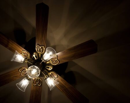 Lighted ceiling fan, showing shadows on ceiling.