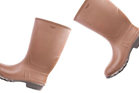 Pair of brown rubber boots walking across photo frame, r to l, white iso.
