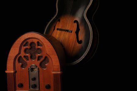 Vintage tabletop radio and acoustic guitar, black iso. Фото со стока